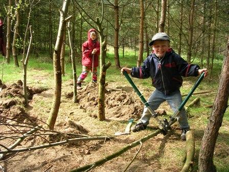 Ein Junge schneidet mit einer Baumschere einen Ast entzwei