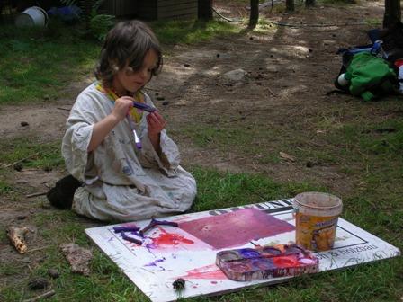 Ein Mädchen sitzt auf dem Waldboden mit einer weißen Platte mit Malutensilien