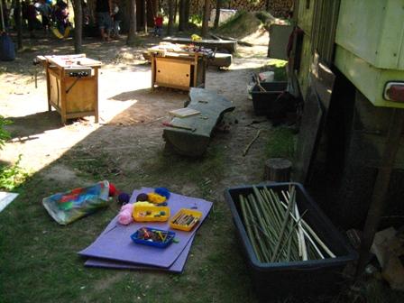 Vor einem Bauwagen sind Werkbänke und Bastelmaterialien zu sehen